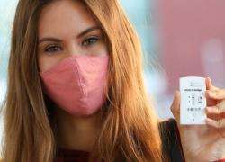 Young woman wearing a pink facemask